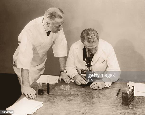 two men working in laboratory, one looking into microscope (b&w sepia) - 20th century stock pictures, royalty-free photos & images
