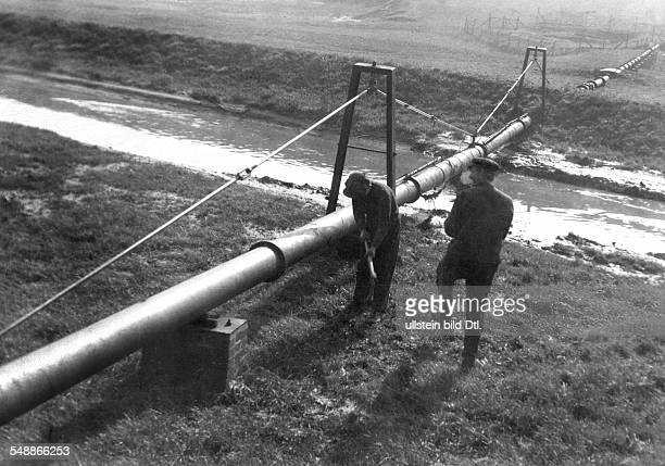 Two men working on a water pipe that was wrought through the germanpolish frontier and is connected with a waterworks in Poland 1930 Photographer...