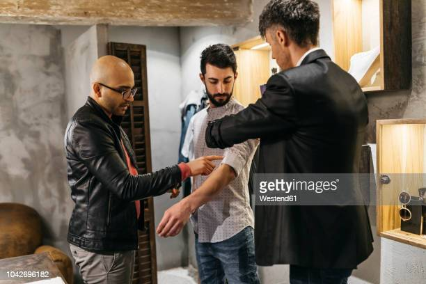 two men working on new stylish look for handsome man in showroom - men fashion stock pictures, royalty-free photos & images