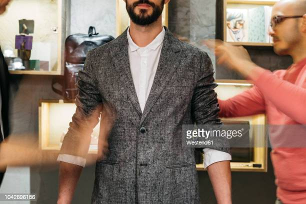 two men working on new stylish look for handsome man in showroom - fast fashion stock pictures, royalty-free photos & images