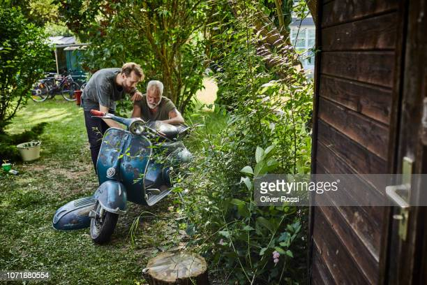 two men working on old motor scooter in garden - adults only stock pictures, royalty-free photos & images