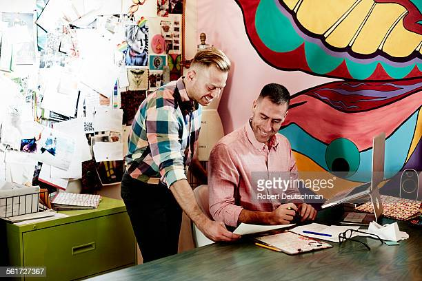 Two men working together in a colorful office.