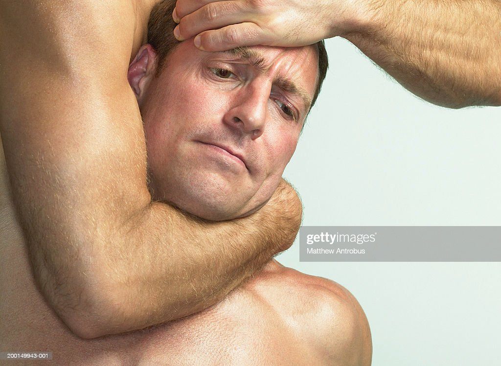 Two men wrestling, one in headlock, close-up : Stock Photo