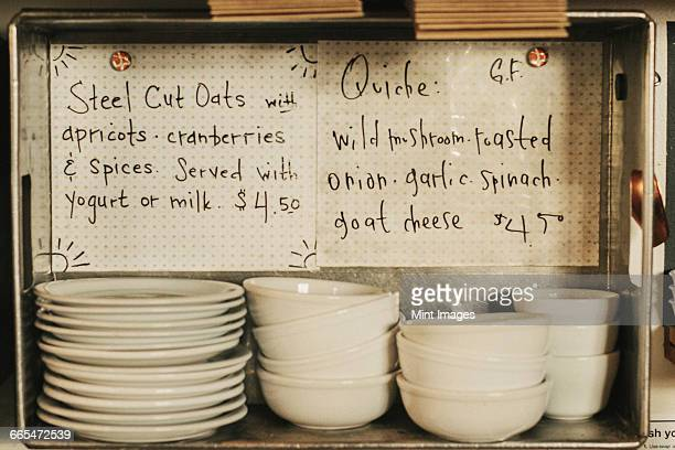 Two menu items written on card. Stacks of plates and bowls.