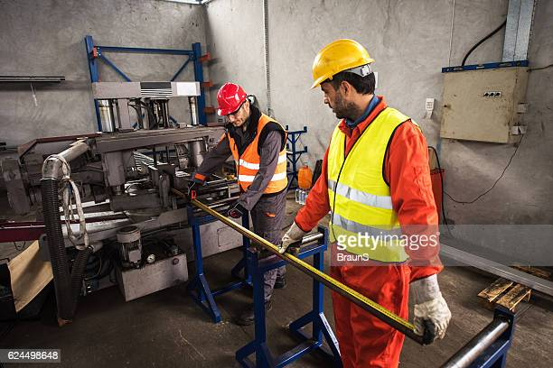 Two metal workers measuring the tube in aluminum mill.