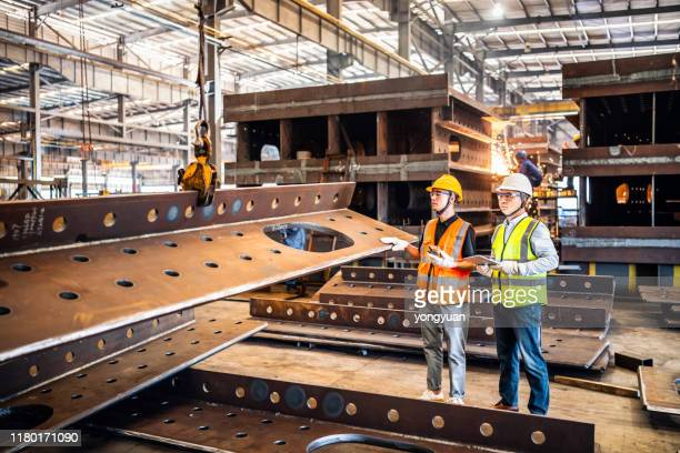 two metal workers operating a crane in a steel factory - crane construction machinery stock pictures, royalty-free photos & images