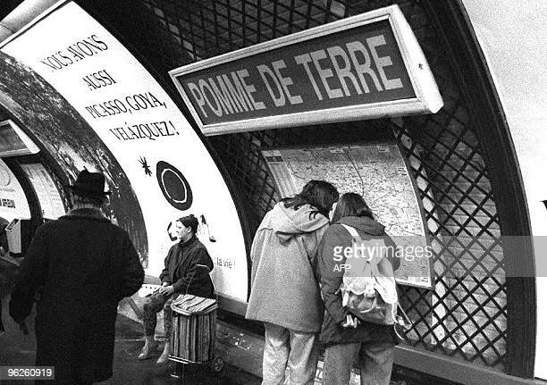 Two metro passengers consult the map 01 April 1994 at the Parmentier station rebaptized 'Pomme de terre' by the RATP or the Parisian Transport who...