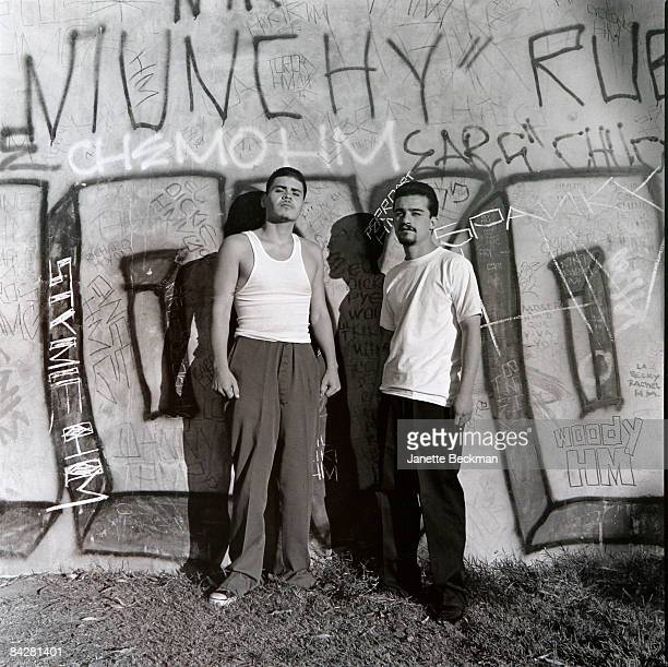 Two Mexican gang members pose against a graffiti tagged wall East Los Angeles 1983