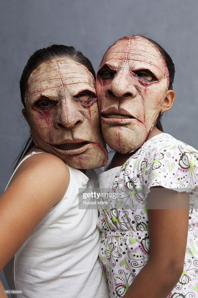Two mexican girls wearing bizarre masks. : Stock Photo