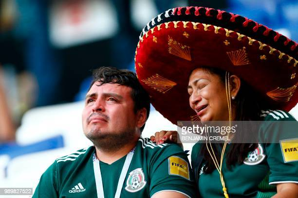 Two Mexico fans react to their team's defeat after the Russia 2018 World Cup round of 16 football match between Brazil and Mexico at the Samara Arena...