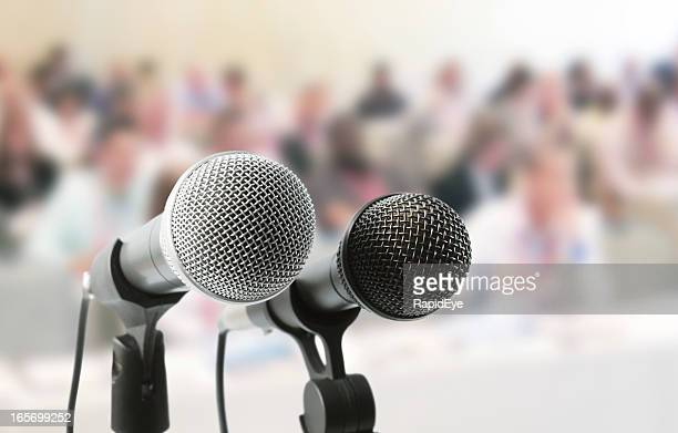 Two microphones await a speaker at meeting in auditorium