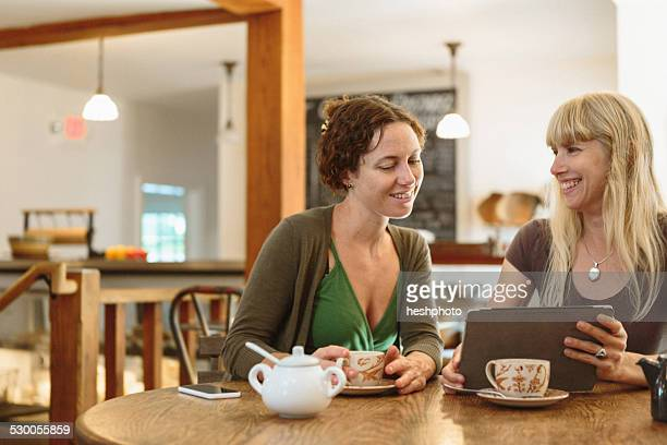 two mid adult female friends looking at digital tablet in country store cafe - heshphoto stockfoto's en -beelden