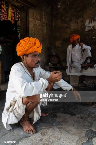two mid adult male gujar villagers in traditional white tunics and bright orange turbans smoke bidis (thin cigarettes/small cigars) in the shade, pushkar, rajasthan, india (two model releases) - james strachan stock pictures, royalty-free photos & images