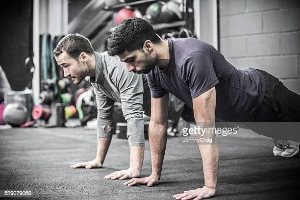 Two mid adult men doing high planks in gym.