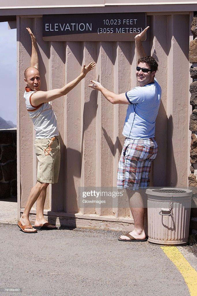 Two mid adult men posing against a wall, Haleakala National Park, Maui, Hawaii Islands, USA : Foto de stock