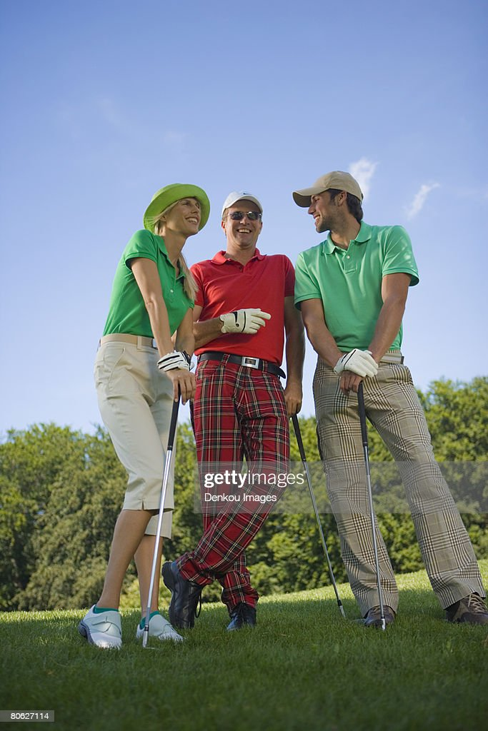 Two mid adult men standing with a mid adult woman on a golf course and holding golf clubs : Stock Photo