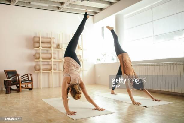 zwei mittelerwachsene frau, die yoga drinnen macht - yogastudio stock-fotos und bilder