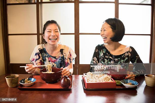 two mid adult woman laughing in japanese restaurant - soba stock pictures, royalty-free photos & images