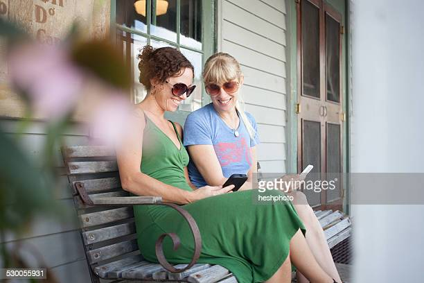 two mid adult woman looking at smartphone on porch - heshphoto stock pictures, royalty-free photos & images