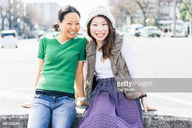 Two mid adult woman relaxing in the city.