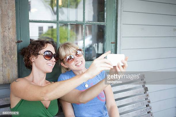 two mid adult woman taking smartphone selfie on porch - heshphoto imagens e fotografias de stock