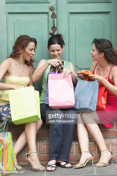 Two mid adult women and a young woman sitting together and holding shopping bags