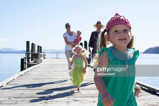 Two mid adult women and daughters strolling and running on pier, New Zealand
