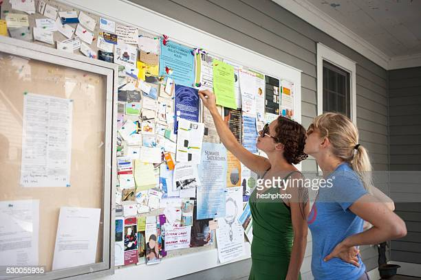 two mid adult women looking up at community notice board - bulletin board stock pictures, royalty-free photos & images