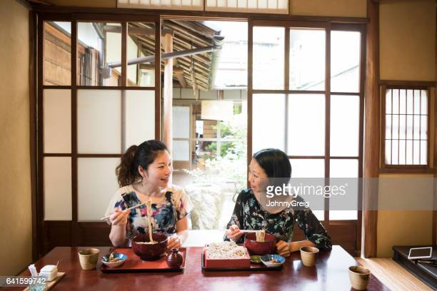 two mid adult women sitting in japanese restaurant eating dinner - soba stock pictures, royalty-free photos & images