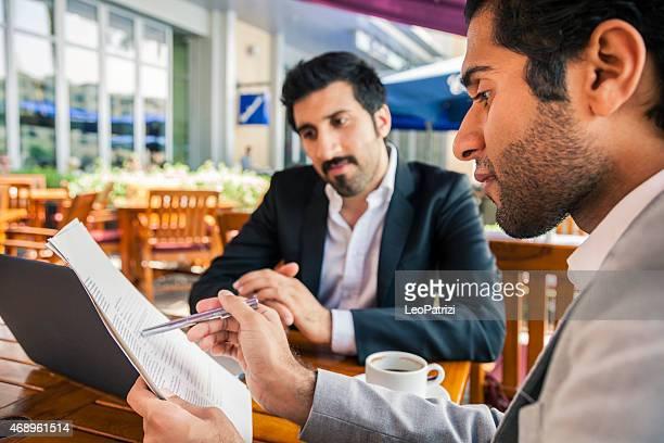 Dois homens de negócios do Oriente Médio preenchimento de documentos em um café