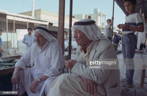 Two Middle Eastern men sit, each wearing a white keffiyeh with a black band, a young boy wearing jeans and a t-shirt standing behind them, in an...