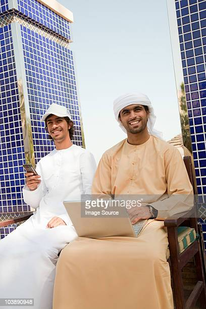 Two Middle Eastern men with laptop and mobile phone