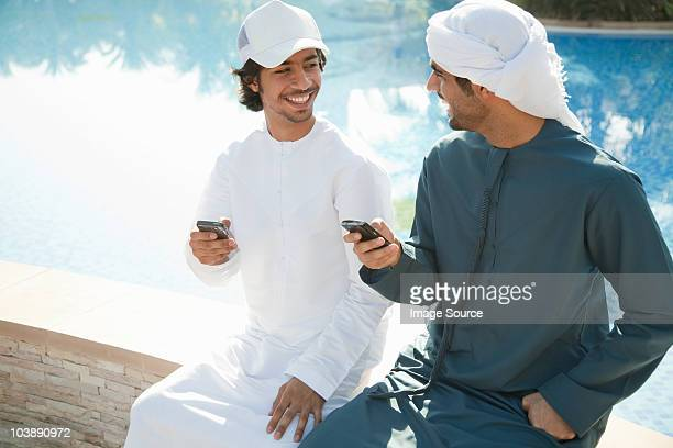 two middle eastern men with mobile phones - baseball cap stock pictures, royalty-free photos & images