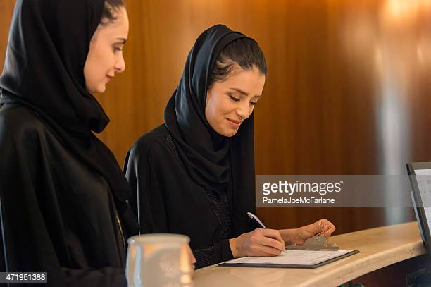 Two Middle Eastern Women Signing in at Spa Reception Counter