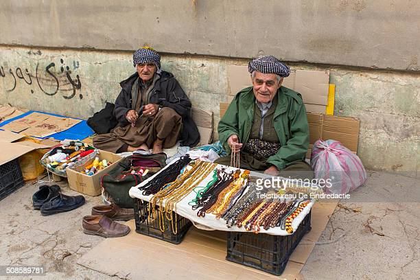 Two middle-aged Kurdish-Iraqi street vendors, wearing traditional baggy trousers and headscarfs, selling muslim prayer chains, yarn and threads, on...