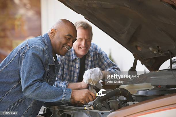 Two middle-aged men repairing a truck with the hood open