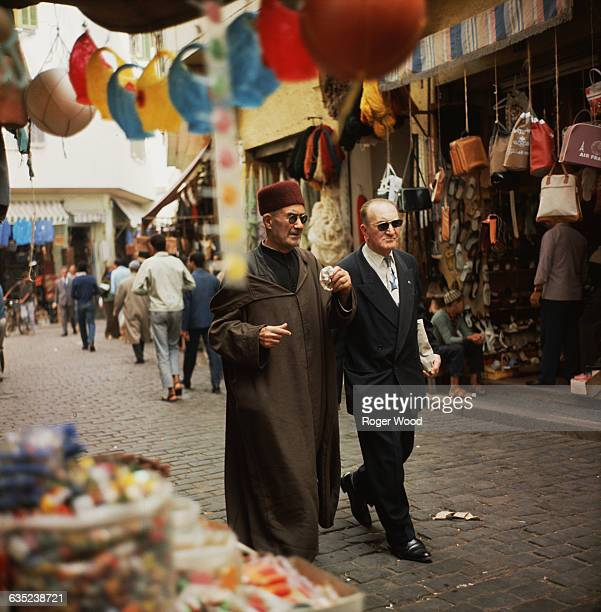 Two middleaged men wearing sunglasses one in a white shirt and business suit and the other in a jellaba and red fez walk together down a stonepaved...
