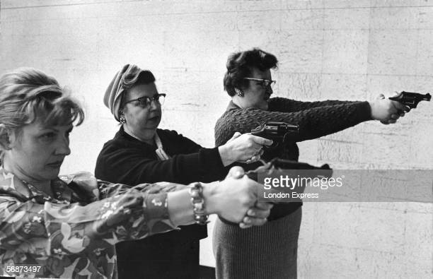 Two middleaged women and one younger woman aim revolvers at a target in a indoor shooting range in Dearborn Michigan 1967 or 1968
