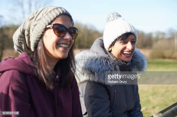 Two middle-aged women sitting in fence in countryside