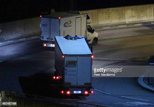 Two migrants cling to the roof of a freight truck as it leaves the Eurotunnel terminal on July 31 2015 in Folkestone England Hundreds of migrants are...