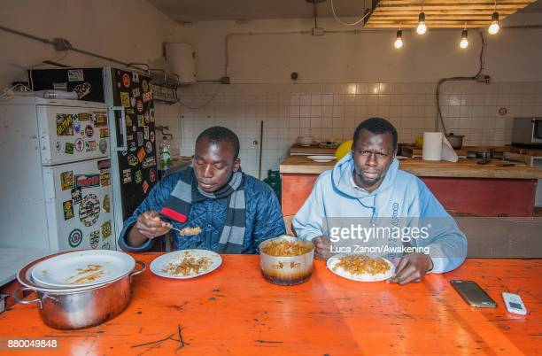 Two migrants eat their meal in the kitchen in the 'CAS' center at the Caracol cooperative on November 27 2017 in Venice Italy The Caracol center...