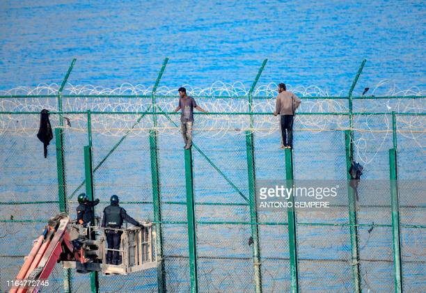 Two migrants force their way into the Spanish territory of Ceuta on August 30, 2019. Over 150 migrants made their way into Ceuta after storming a...