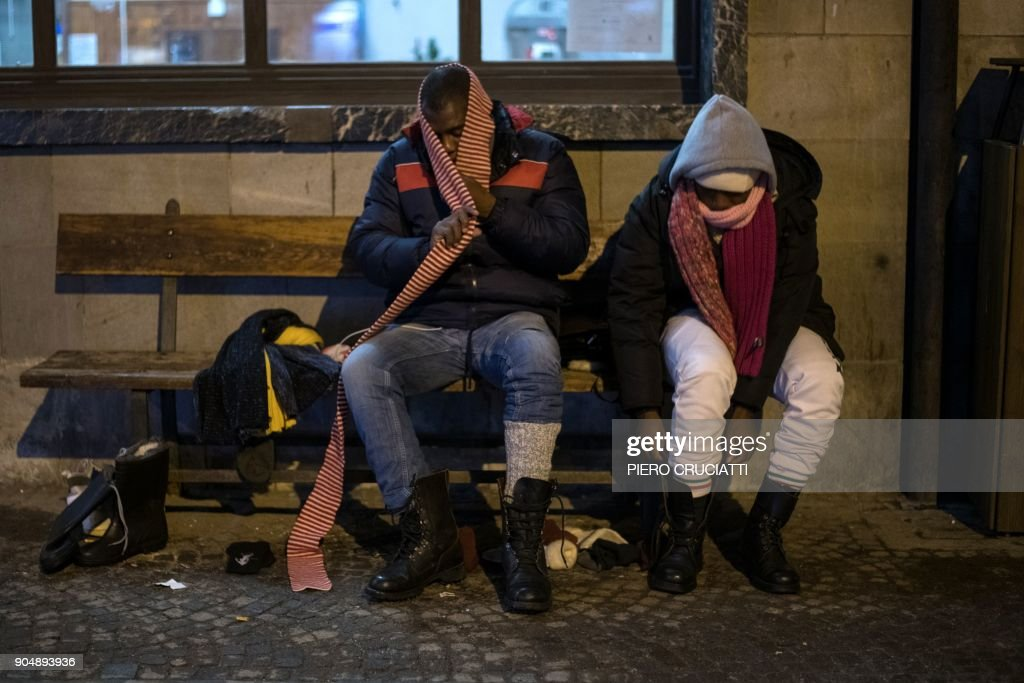 Two migrants from Guinea put on winter shoes and clothes donated by a charity organisation in Bardonecchia, Italy, on January 13, 2018. Migrants are now trying to reach France crossing the Italian Alps by the snow-covered pass Colle della Scala (Col de l'Echelle) despite snow and bad weather conditions. / AFP PHOTO / Piero CRUCIATTI