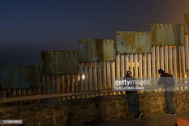 Two migrants from the Mexican southern state of Chiapas lean against a rail next to the US/Mexico border fence in Tijuana Baja California state...