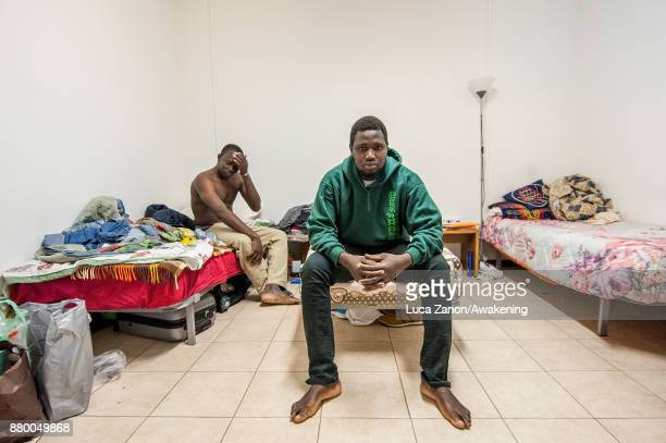 Two migrants pose for a portrait in their room in the 'CAS' center at the Caracol cooperative on November 27 2017 in Venice Italy The Caracol center...