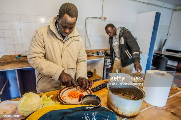 Two migrants prepare lunch in the kitchen in the 'CAS' center at the Caracol cooperative on November 27 2017 in Venice Italy The Caracol center hosts...