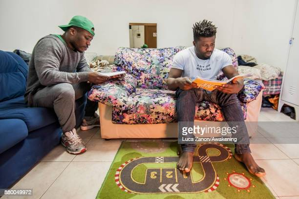 Two migrants study Italian in their room in the 'CAS' center at the Caracol cooperative on November 27 2017 in Venice Italy The Caracol center hosts...
