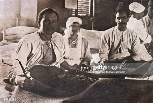 Two military officers injured hospitalized here playing chess assisted by a Red Cross nurse one of the two is smoking a pipe Private snapshot sent...
