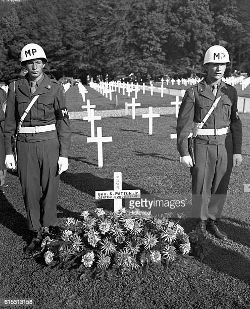 Two military police officers guard the grave marker of General George Patton Jr decorated with flowers placed on the grave by Gen Dwight Eisenhower...