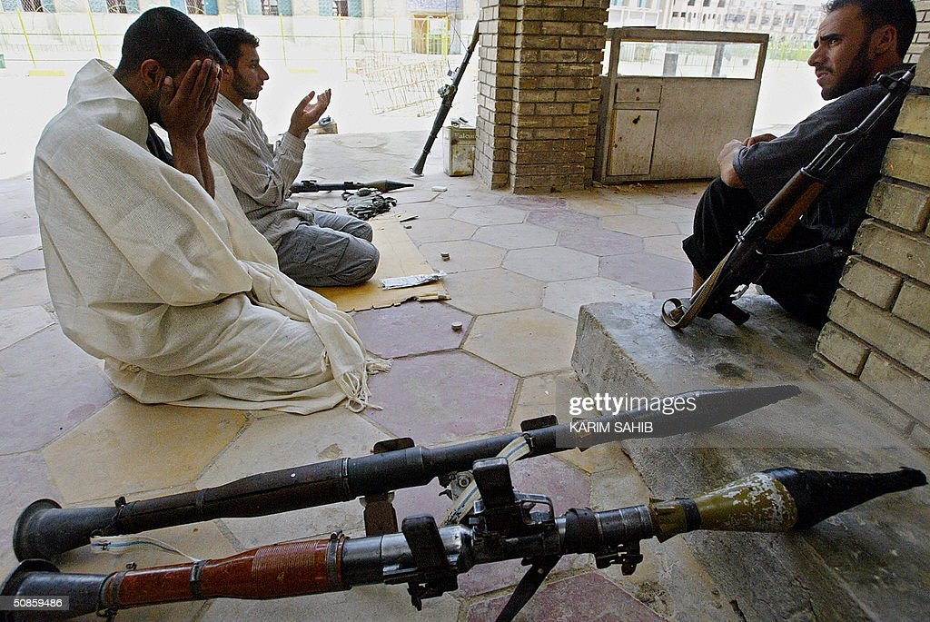 Two militiamen loyal to radical Shiite cleric Moqtada Sadr pray near their weapons 20 May 2004 as another one keeps watch over the area of the Imam Hussein shrine in Karbala, 110 kms south of Baghdad. Nine civilians were killed and 16 others wounded overnight in Karbala during continuous clashes between US forces and Sadr's Army of Mehdi militia. AFP PHOTO/Karim SAHIB